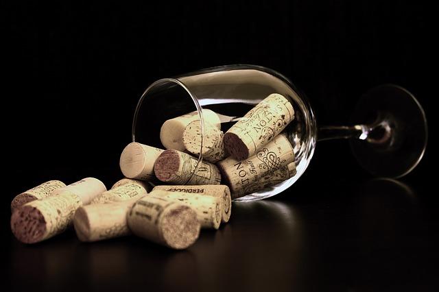 sklenka vína a korkové zátky